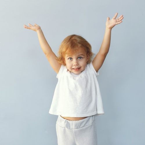 Child in a studio. Little girl on a blue background. Girl in a white t-shirt.